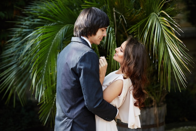 Gorgeous bride with long curly hair and bridegroom standing close to each other at green leaves, wedding photo, beautiful couple, wedding day.
