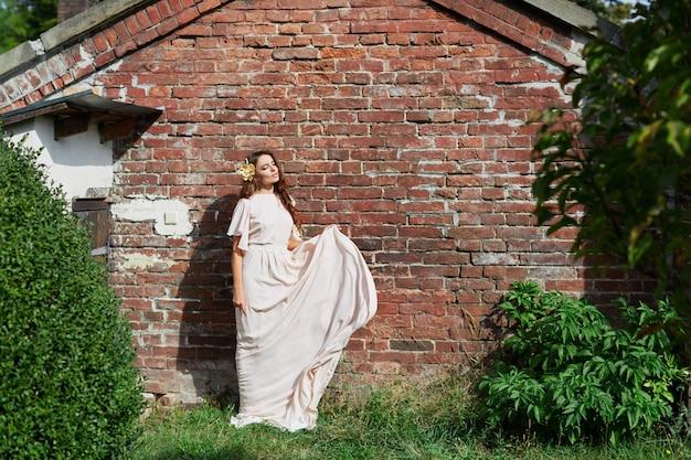 公園の背景、結婚式の写真、肖像画に立っているウェディングドレスの長い巻き毛のゴージャスな花嫁。