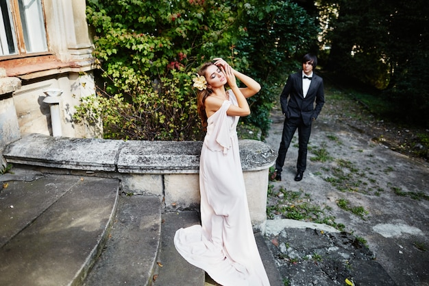 Gorgeous bride with long curly hair in wedding dress standing at park, wedding photo.