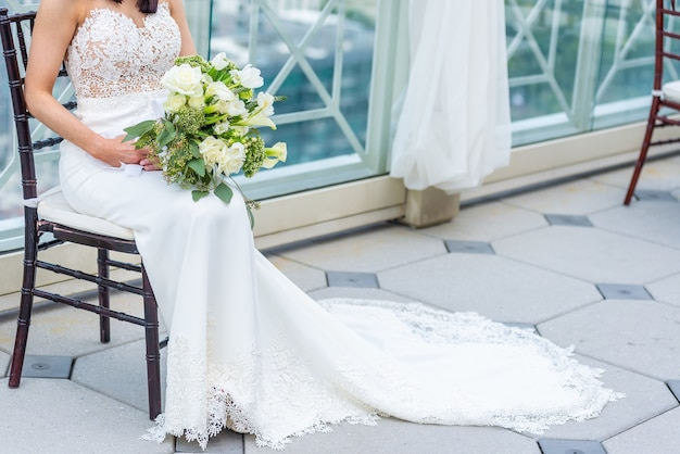 Gorgeous bride with a luxury wedding dress sitting on a chair holding a bridal bouquet