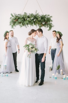 Gorgeous bride with peony bouquet and stylish groom posing with bridesmaids and groomsman on wedding day