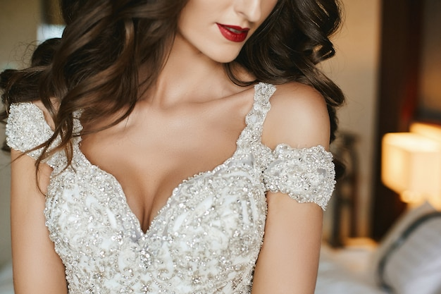 웨딩 메이크업과 신부 드레스에 긴 곱슬 머리를 가진 화려한 신부. 인테리어에서 포즈 우아한 웨딩 드레스에서 패션 모델. 럭셔리 드레스에 젊은 여자 크리스탈 장식. 웨딩 패션
