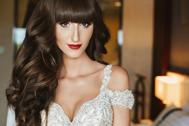 Gorgeous bride with wedding makeup and long wavy hair in bridal dress. fashion model in elegant wedding dress posing at interior. young woman in luxury dress decorated with crystals. wedding fashion