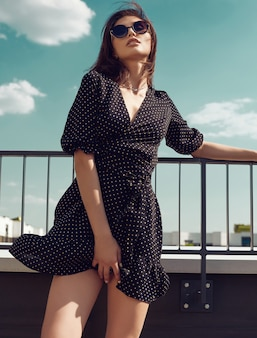 Gorgeous bright brunette woman in fashion dress posing on the roof of a building