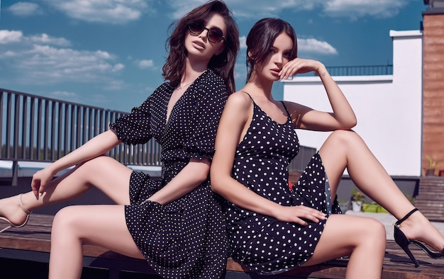 Gorgeous bright couple of brunette women in vivid dresses posing on the roof