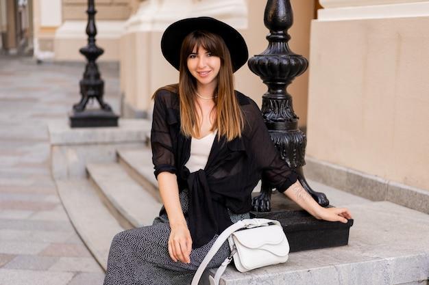 Splendida donna brunetta in elegante abito autunnale e cappello posteriore in posa per strada nella vecchia città europea