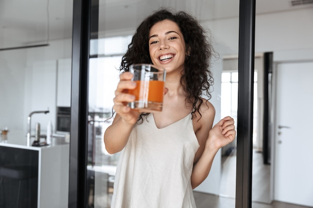 オレンジジュースのガラスを見せながら、笑顔のシルクレジャー服を着てゴージャスなブルネットの巻き毛の女性