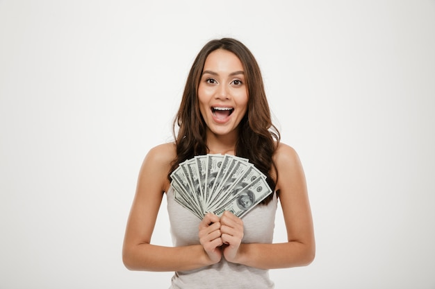 Gorgeous brunette female model with long hair holding fan of 100 dollar bills, being rich and happy over white wall