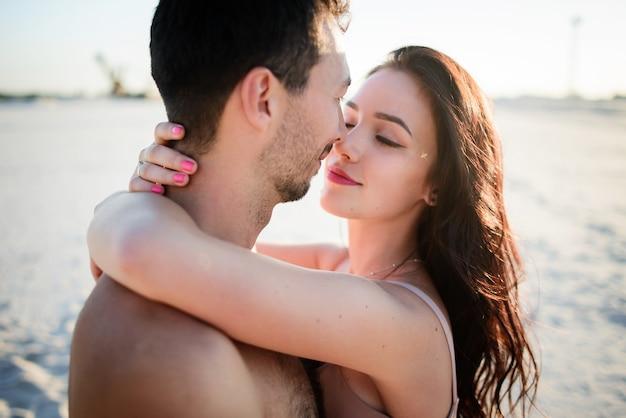 Великолепная брюнетка обнимает мужчину на белом песке