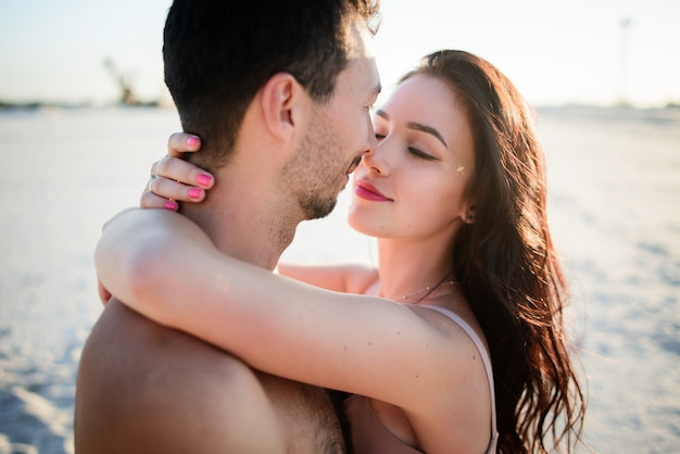 Gorgeous brunette  hugs her  man on white sand