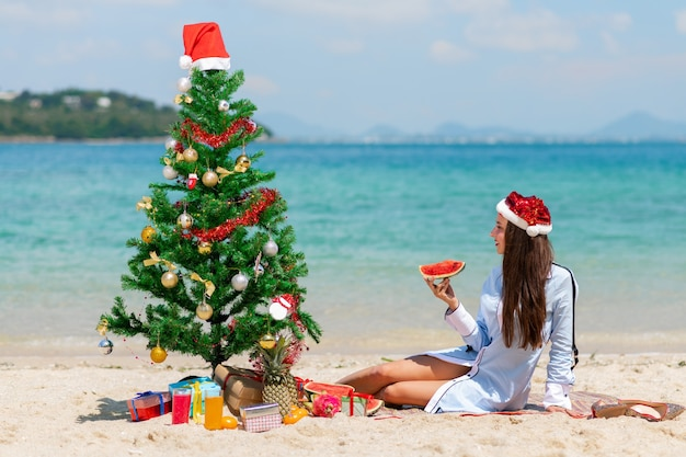 A gorgeous brunette sits with a fresh watermelon near a dressed up fir tree on the beach.