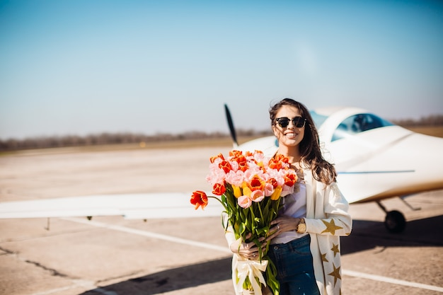Gorgeous brunette stands with large bouquet of tulips before an airplane