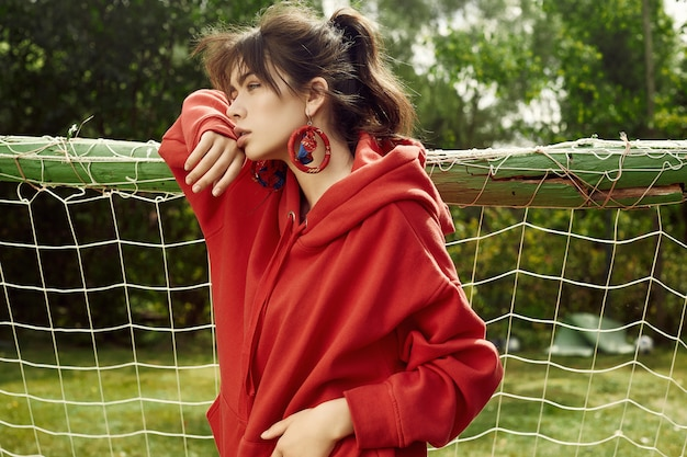 Gorgeous brunette woman in fashion red hoodie on sports field