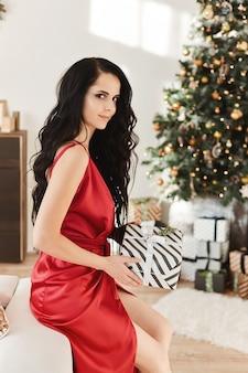 Великолепная брюнетка в красном вечернем платье держит рождественскую подарочную коробку