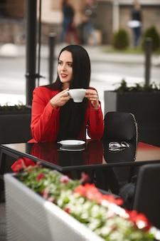 カフェで赤いスーツでゴージャスなブルネットの女性