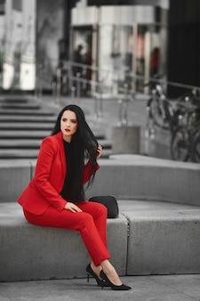 Великолепная брюнетка женщина в красном костюме