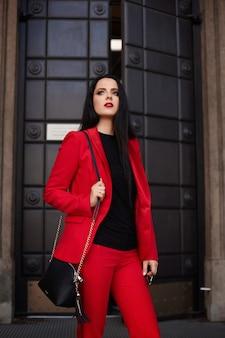 赤いスーツでゴージャスなブルネットの女性