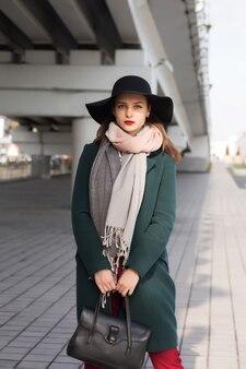 街でポーズをとって緑のコートと黒い帽子のゴージャスなブルネットの女性