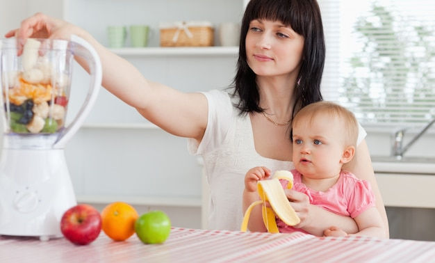 Gorgeous brunette woman putting vegetables in a mixer while holding her baby on her knees