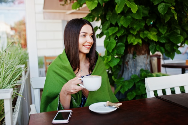 Великолепная брюнетка женщина сидит на столе в кафе плед с чашкой кофе.