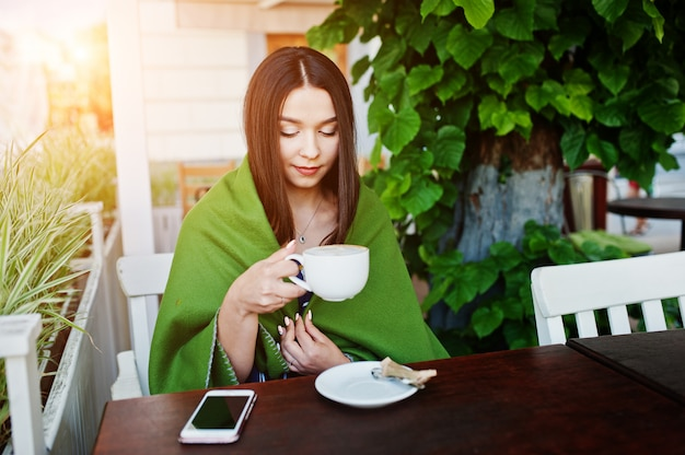 Gorgeous brunette woman sitting on the table in cafe cover plaid with cup of coffee.