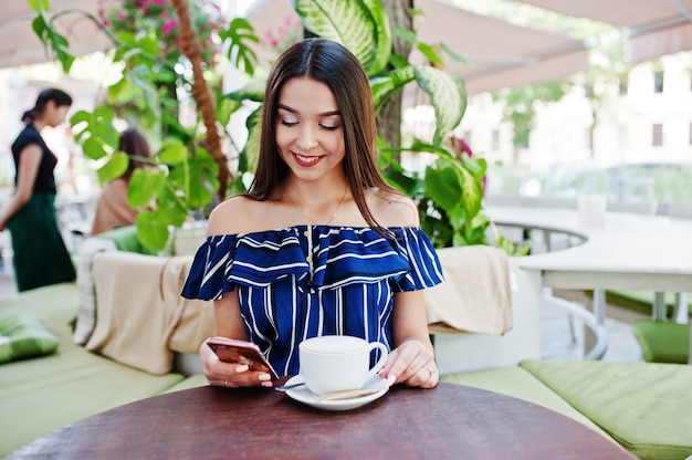 Gorgeous brunette woman sitting on the table in cafe with cup of coffee.
