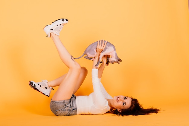 Gorgeous brunette woman smiling, holding sphynx kitten, posing on grey and yellow studio background.