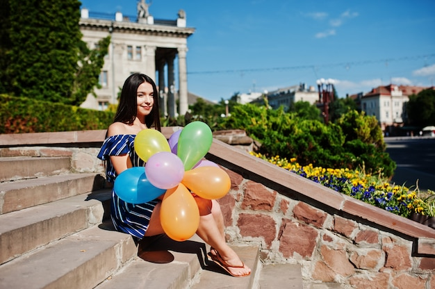 Gorgeous brunette woman at street of city with balloons at hands.