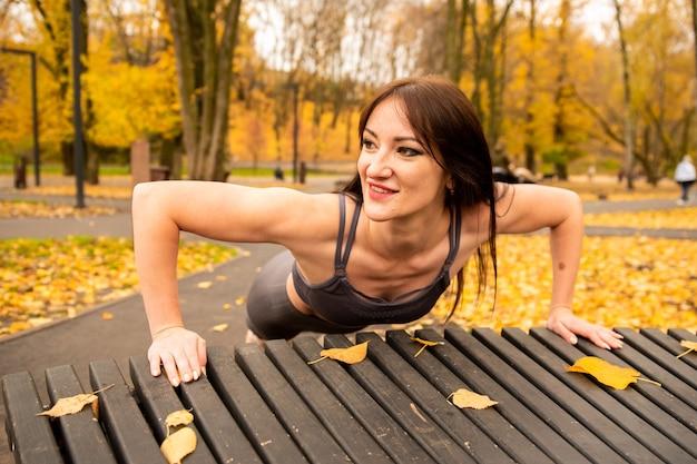 秋の公園でウォーミングアップと腕立て伏せをしているゴージャスなブルネットの女性。彼女は黄色の葉でベンチから腕立て伏せをします。彼女は微笑んでいる。