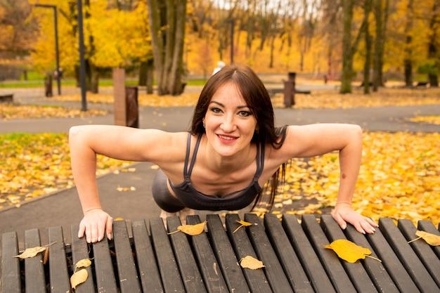 秋の公園でウォーミングアップと腕立て伏せをしているゴージャスなブルネットの女性。彼女は黄色の葉でベンチから腕立て伏せをします。彼女はまっすぐ見て笑っている。