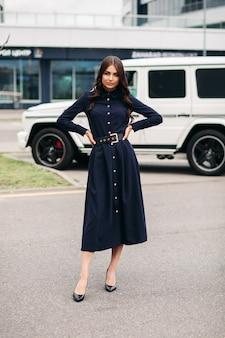 Великолепная брюнетка с длинными волнистыми волосами в темном платье на пуговицах