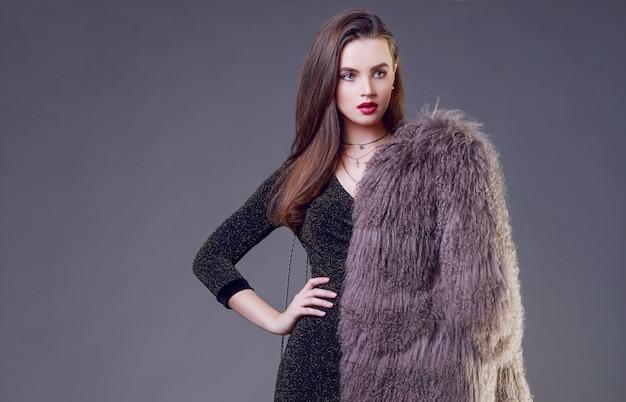 毛皮のコートとカクテルドレスのポーズを着ている赤い唇でゴージャスなブルネットの女性
