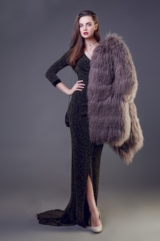 Gorgeous brunette woman with red lips wearing furry coat and cocktail dress posing