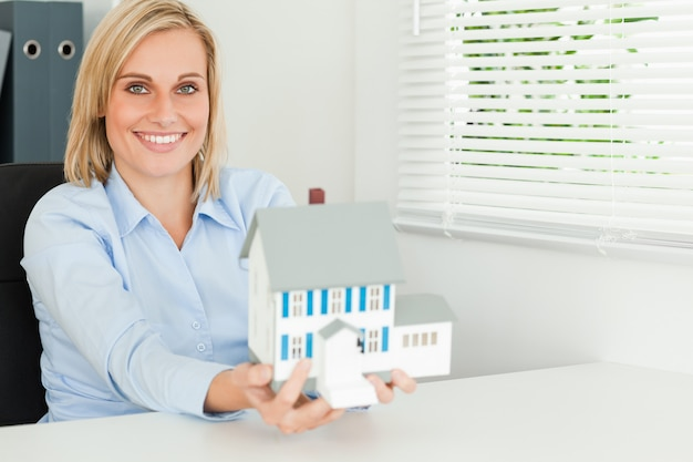 Gorgeous businesswoman presenting model house looks into camera