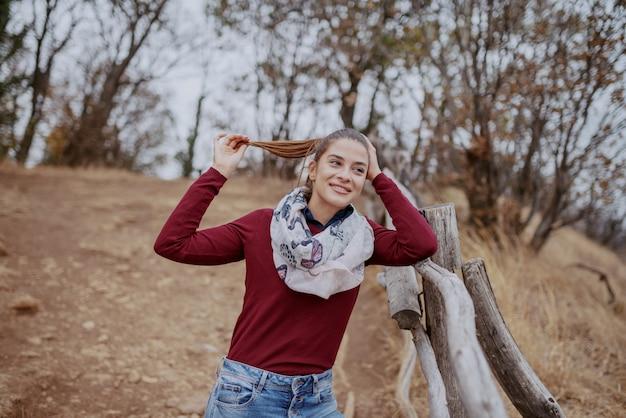 ゴージャスな白人ブルネットは木製のフェンスにもたれて、美しい景色を見てカジュアルな服を着てください。秋の時間。