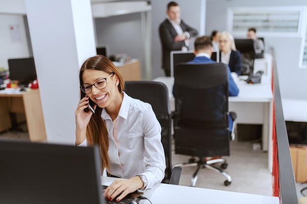 Gorgeous caucasian businesswoman in formal wear using computer and talking on the phone. in background her coworkers working.