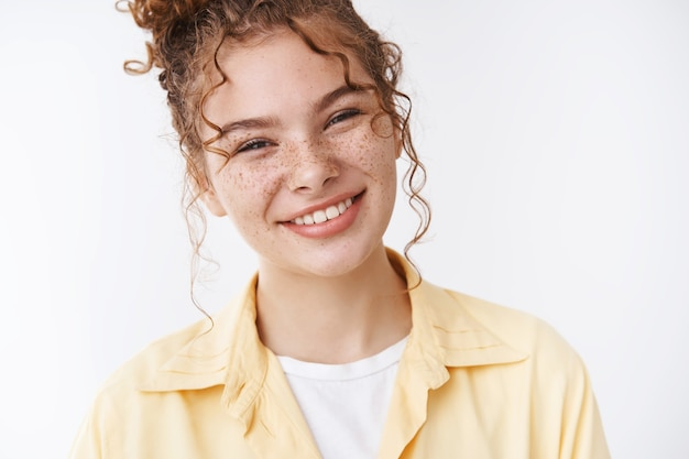 Gorgeous caucasian ginger girl freckles messy curly bun tilting head friendly pleasantly smiling expressing optimism, feel happy relaxed, standing white background sharing positive memories
