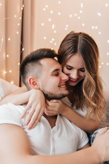 부드럽게 포용 남자 친구 화려한 백인 여자. 갈색 머리 남편과 함께 시간을 보내는 물결 모양의 머리를 가진 웃는 아가씨의 실내 사진.