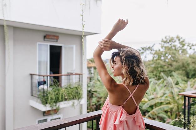 ホテルのバルコニーで伸びるピンクの服装でゴージャスな白人の女の子。テラスから街の景色を楽しむ壮大な巻き毛の女性。
