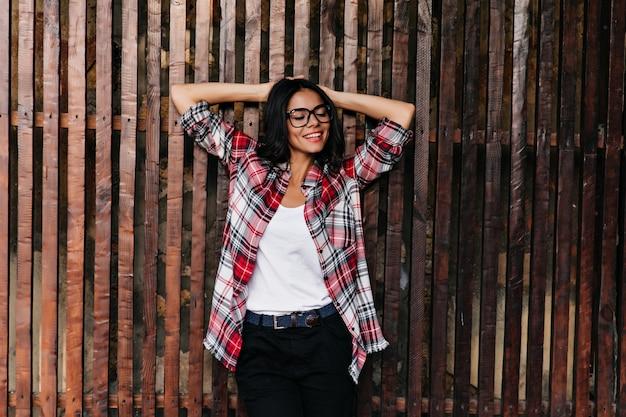 Splendida signora caucasica in abbigliamento casual primaverile godendo buona giornata. foto all'aperto di giovane donna rilassata in bicchieri in piedi sulla parete in legno.