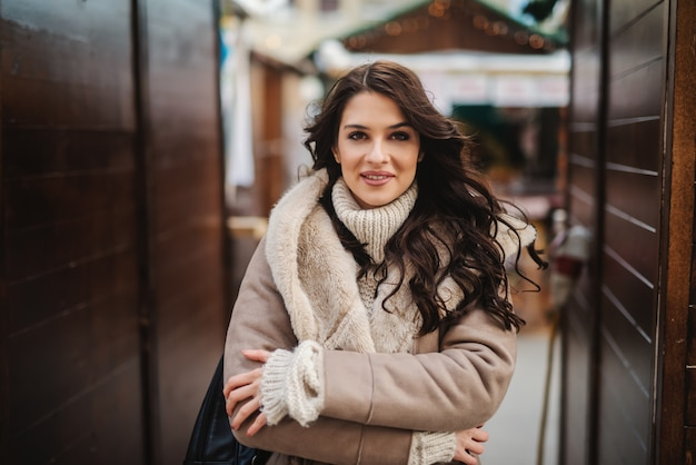 Gorgeous caucasian woman in coat standing on the street on cold weather with crossed arms.
