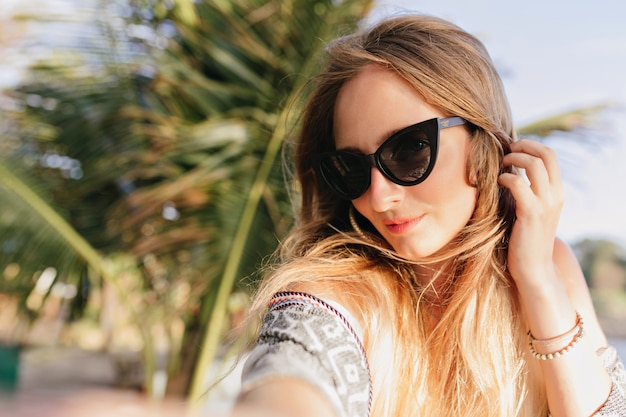 Gorgeous caucasian woman making selfie at beach with palm trees. outdoor photo of winsome girl in black sunglasses spending vacation in exotic country.
