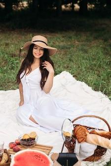 パン屋とゴージャスな白人女性。夏の帽子の美しいブルネットの女性のストックフォトの肖像画