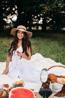 パン屋とゴージャスな白人女性。夏の日に緑の公園に立っている彼女の手で茶色の編み枝細工のバスケットで新鮮な自家製パン屋を示す白いドレス。