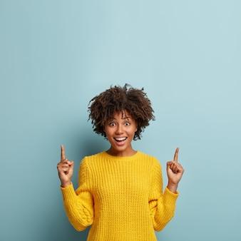 アフロの髪型を持つゴージャスな陽気な笑顔の女性は、上向き、クールなプロモーションや素晴らしいオファーを示し、黄色のセーターを着て、アドバイスを与え、青い背景に対してポーズをとる