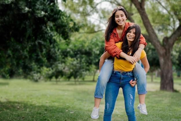 Великолепные веселые молодые подруги из аргентины веселятся в парке, улыбаясь