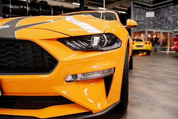 屋内に立っている豪華な黄色い自動車の正面のゴージャスなクローズアップビュー