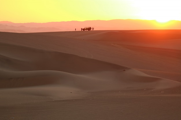 Gorgeous color layer of sunset over the sand dune of huacachina desert with the silhouette of dune baggy and people