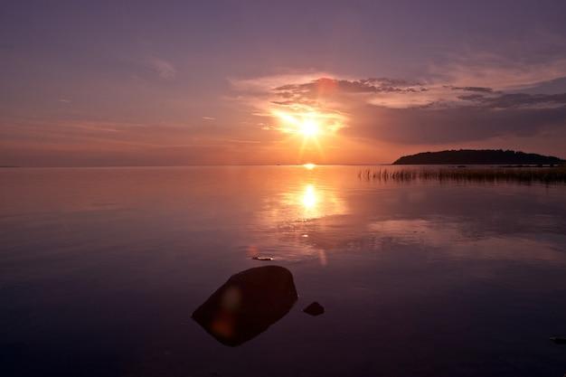 바다의 섬이 내려다 보이는 반사와 함께 화려한 화려한 분홍색과 파란색 일몰 하늘