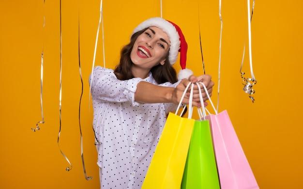 赤いサンタの帽子と白いシャツを着たゴージャスな自信を持って幸せな現代の女性は、クリスマスと新年の季節を祝っている間、孤立した黄色の背景にポーズをとっています